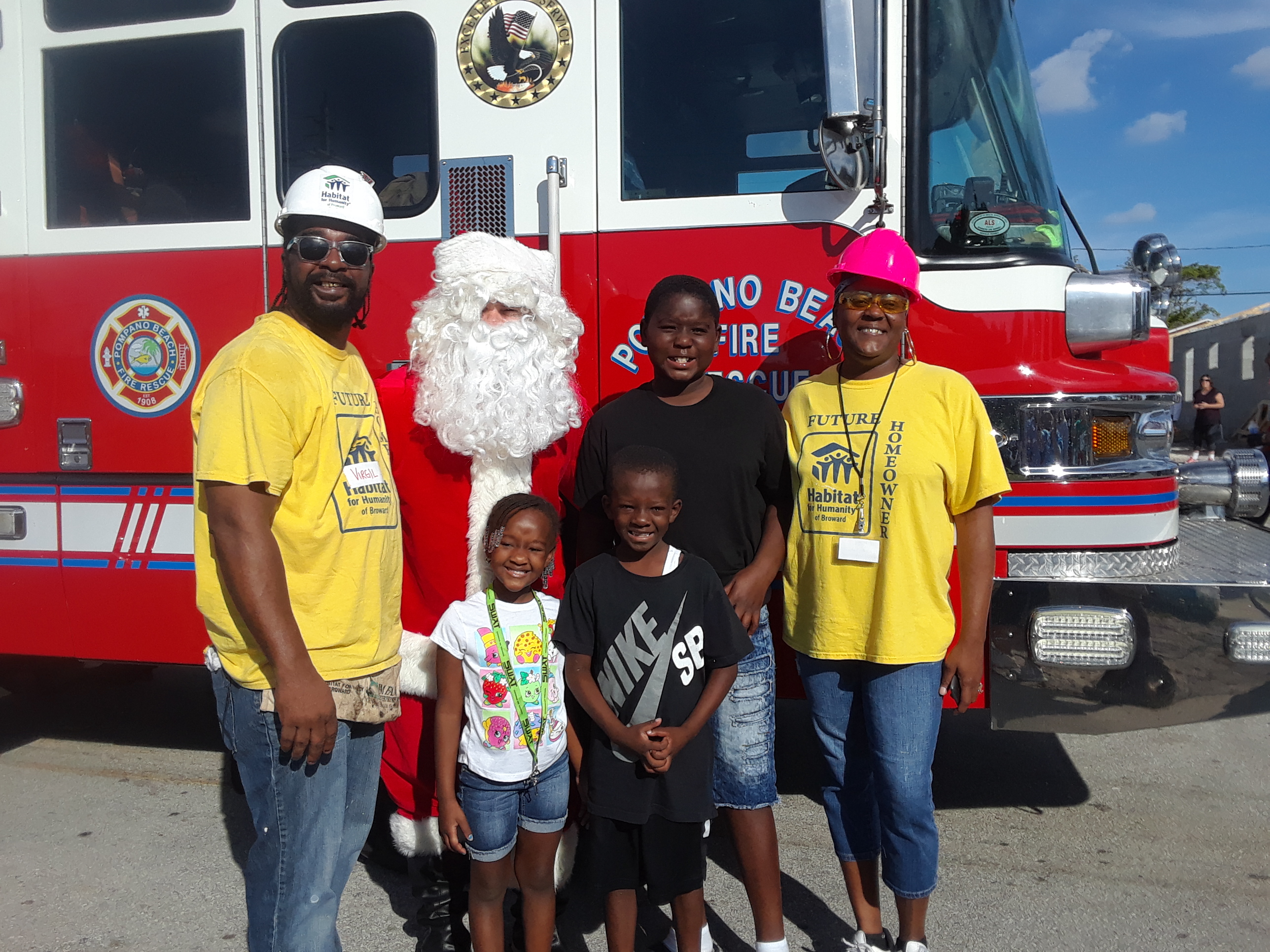 image_James family with Santa in front of a red fire truck