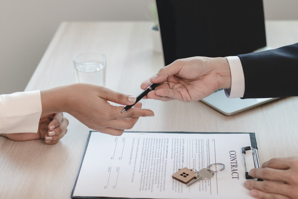 Real Estate Agent Handing a Pen to the Client to Sign the House Purchase Contract