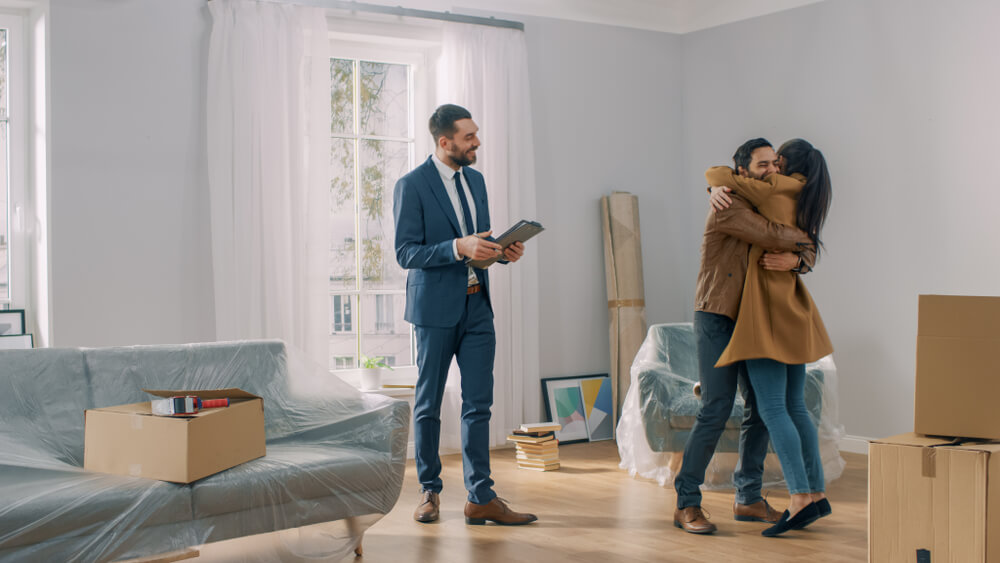Young Couple Becoming Homeowners, Embraces and Hugs Each Other.